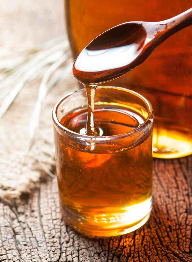 Honey dripping from a wooden spoon into a glass jar