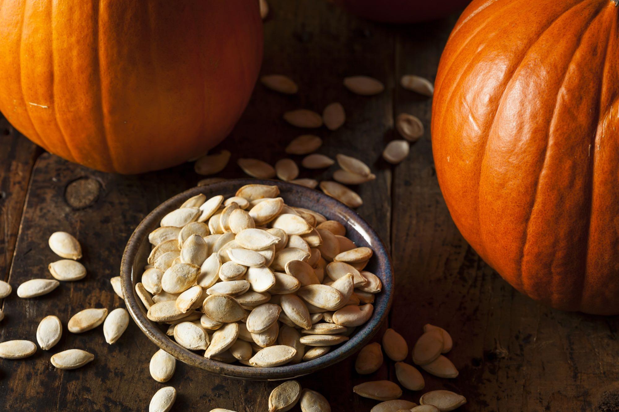 Bowl of pumpkin seeds between two pumpkins