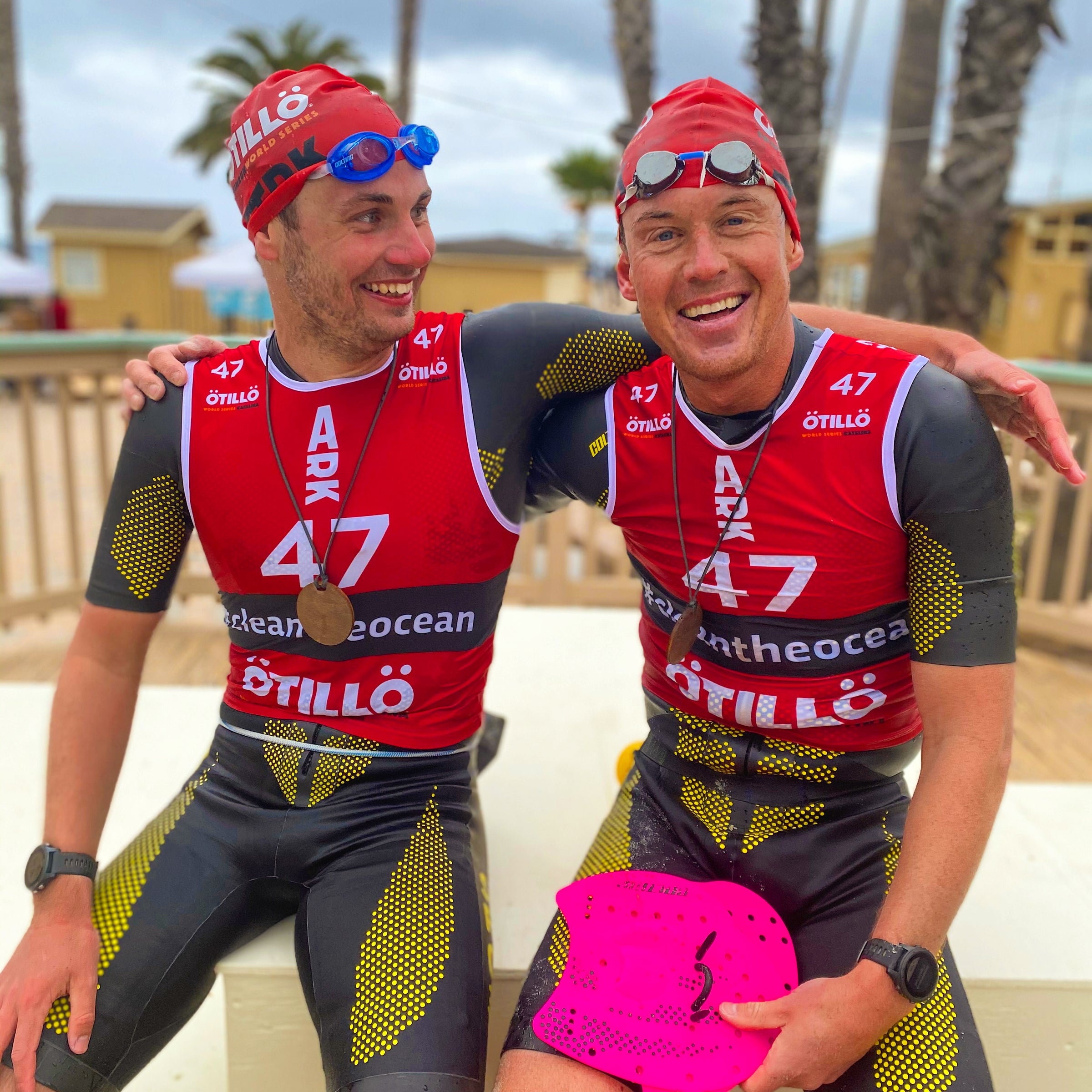 Two men rest in their swimrun gear with arms around each other, smiling