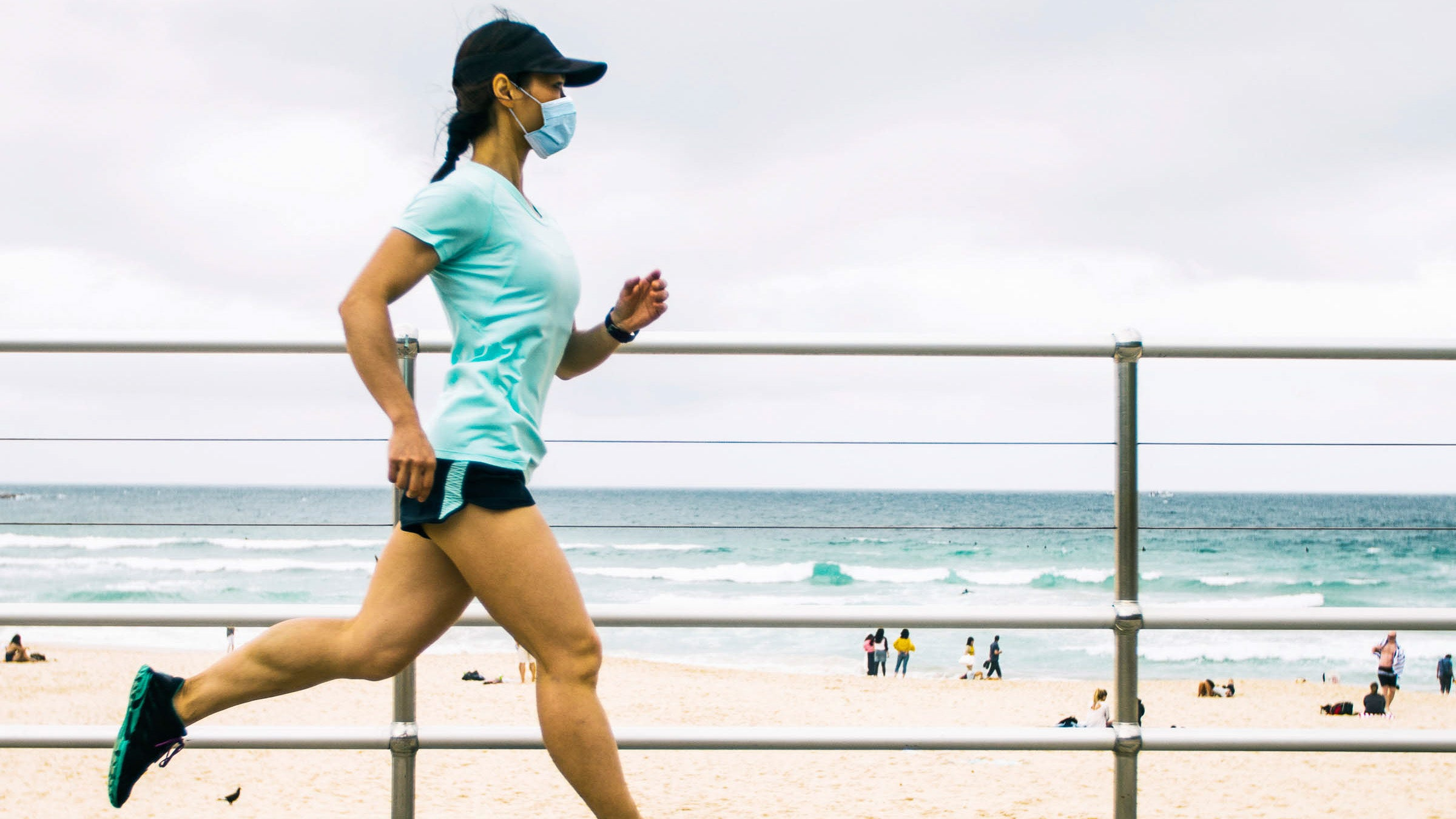 Woman jogging wearing face mask.
