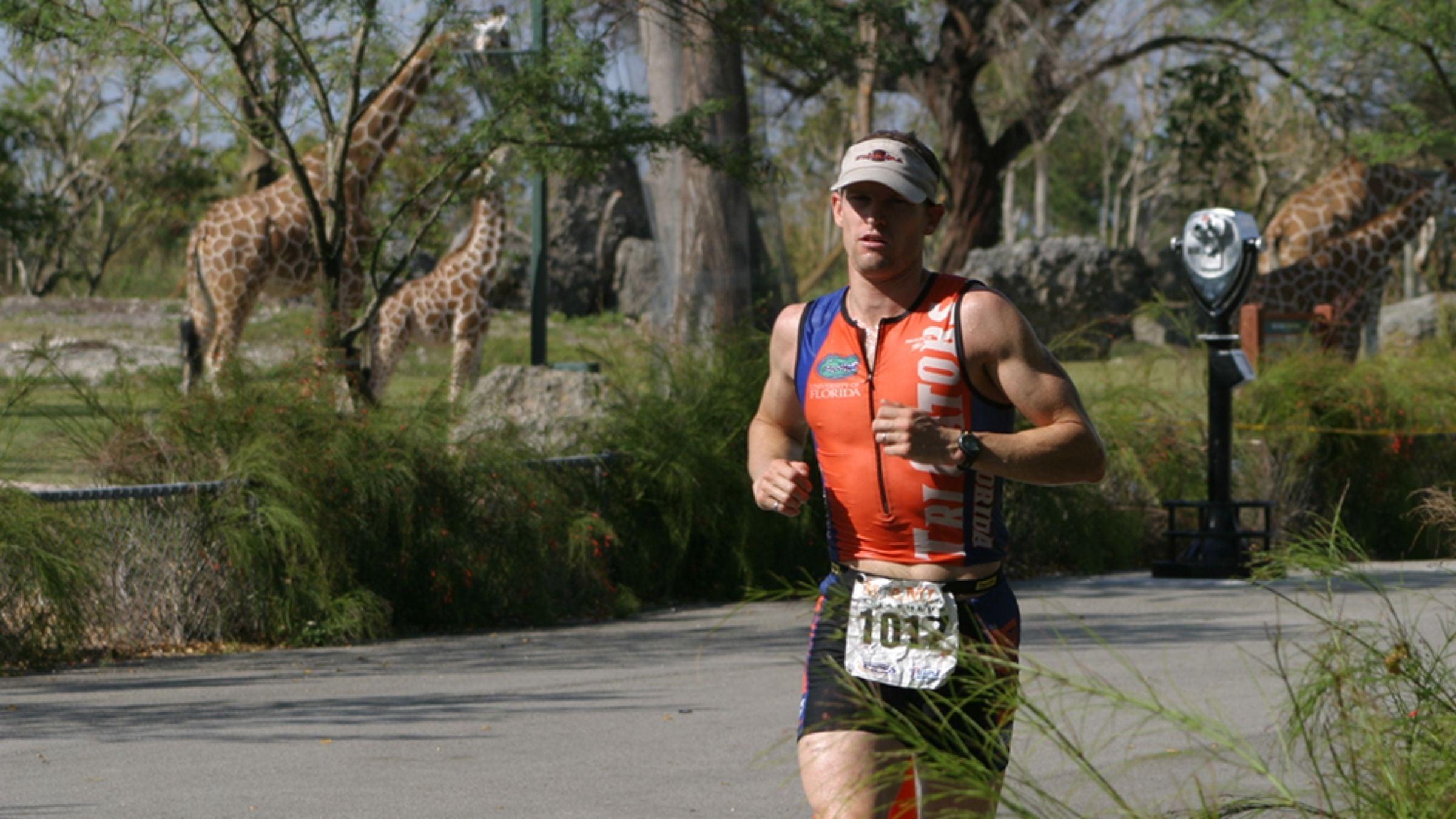 A man runs through the giraffe habitat at the zoo during the Miami Man triathlon.