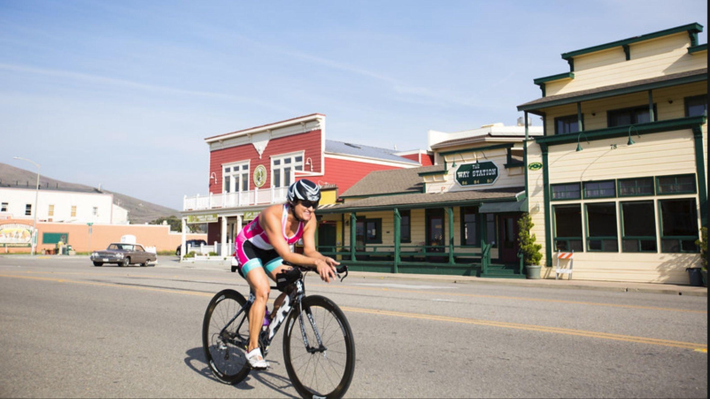 A woman on a triathlon bike smiles as she rides through the Morro Bay Triathlon.